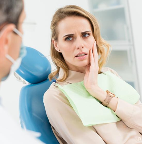 A young woman holding her cheek in pain at the dentist office