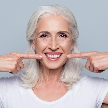 Older woman pointing to her flawless smile