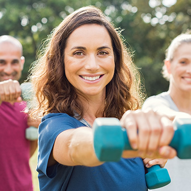 Smiling woman holding exercise weight