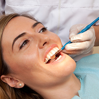 Woman receiving oral cancer screening