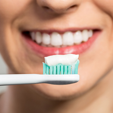 Closeup of smile and toothbrush with toothpaste