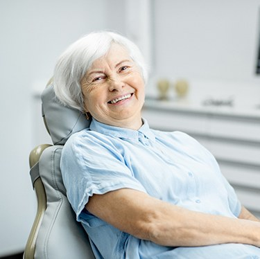 An older woman smiling in the dentist's chair after receiving dental implants in Waco