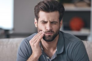 pained man at home wondering if he has an urgent dental emergency