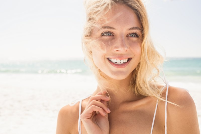 Woman with dental implants in Waco smiling on a beach