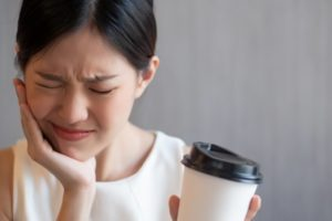 person drinking coffee and holding their mouth in pain