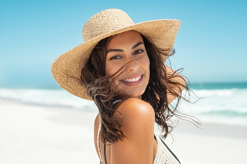 a young woman wearing a hat and smiling while on the beach