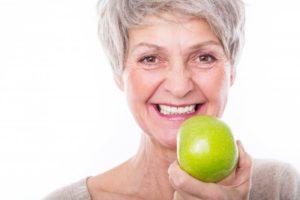 older woman preparing to eat apple