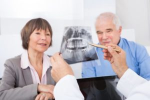 A dentist showing an X-ray to patients.