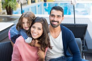 young family smiling beside a pool