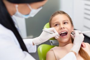 A hygienist examining a child's teeth.