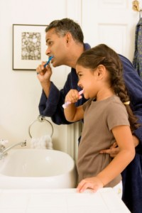 Father and daughter brushing teeth with toothbrush recommended by Waco Dentist Premier Family Dental
