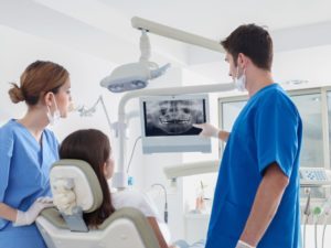 dentist showing dental x-ray to patient who needs wisdom tooth extractions in Waco