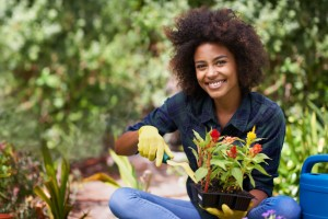 Woman with a beautiful smile planting healthy foods recommended by the waco dentist