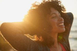 woman smiling in the sunset after wearing clear braces in Waco